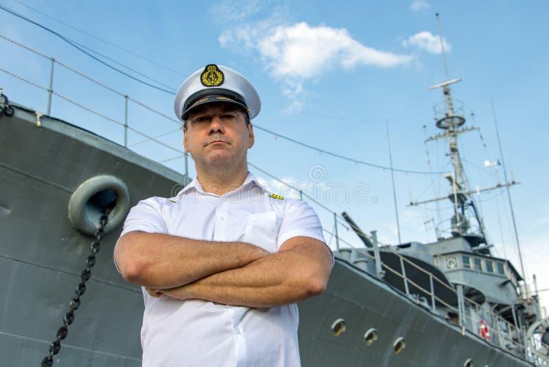 站立在船坞的上尉在军舰前 库存照片