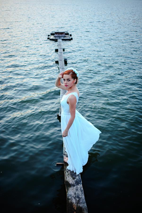 站立在船坞的新娘在一件白色礼服的水附近 库存照片