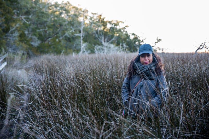 站立在芦苇的妇女在北卡罗来纳国家公园沼泽地  免版税库存照片