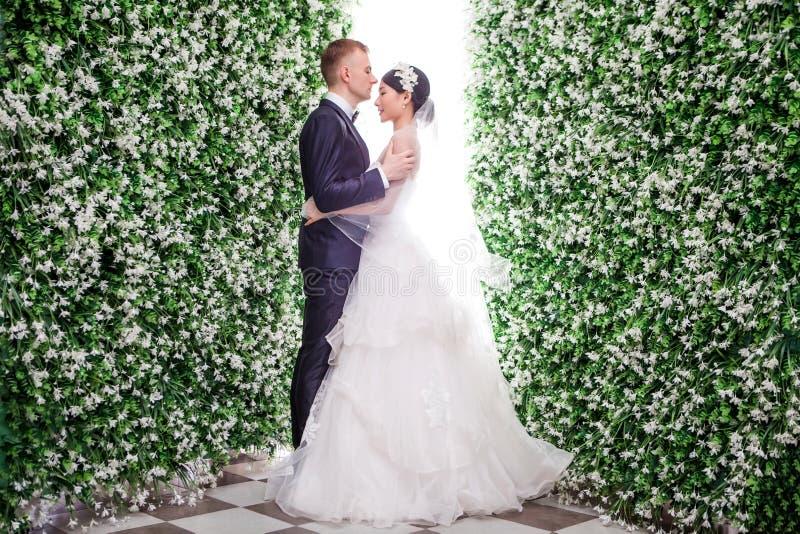 站立在花装饰中的浪漫婚礼夫妇侧视图  免版税库存图片