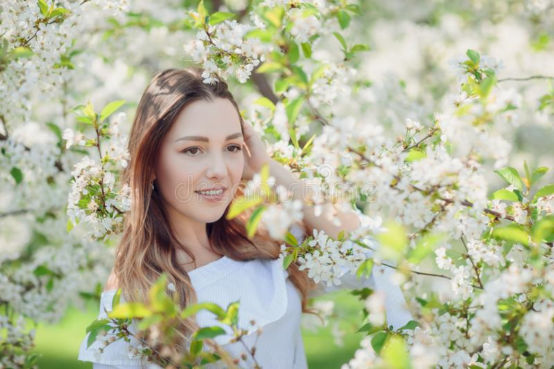 站立在苹果树附近的美丽的年轻深色的妇女 免版税库存照片