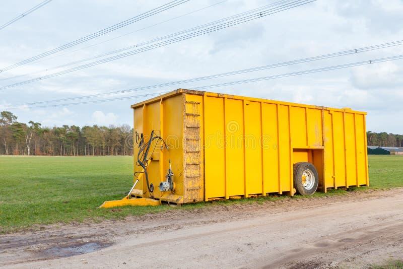 站立在草甸的大黄色肥料坦克 库存照片
