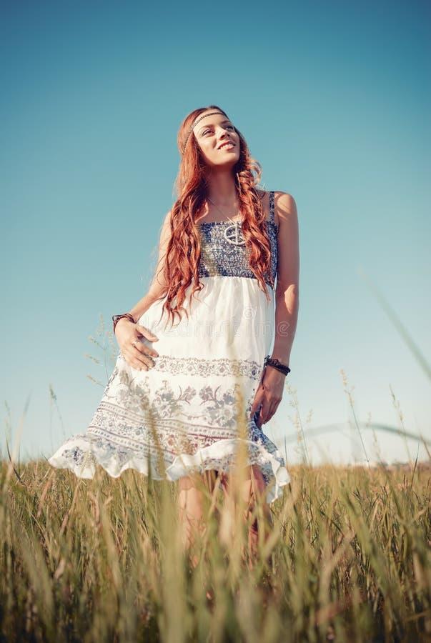 站立在草甸的微笑的俏丽的嬉皮妇女 免版税库存图片