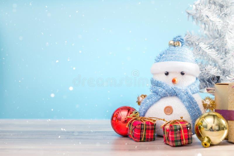 站立在蓝色冬天圣诞节雪背景中的愉快的雪人 免版税图库摄影