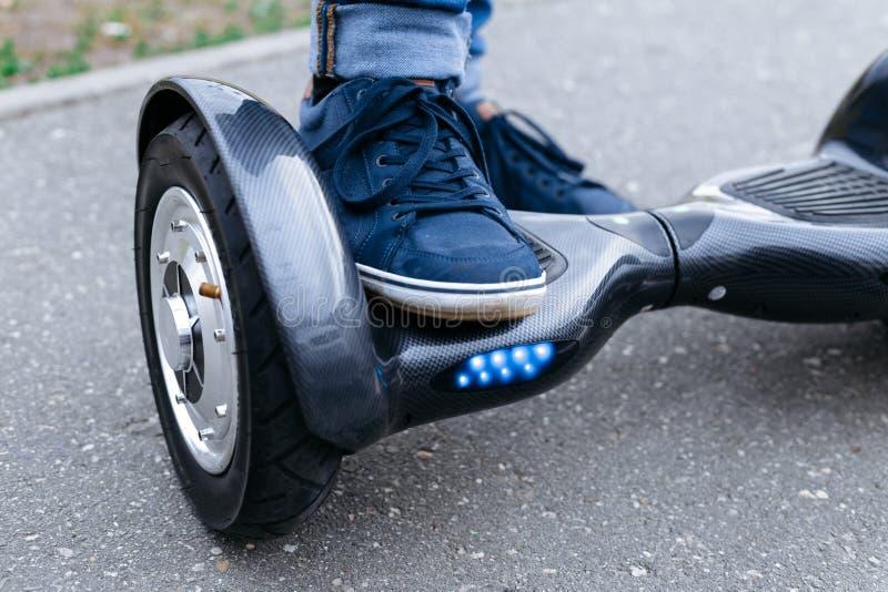 站立在蓝色平台的运动鞋和牛仔裤的腿人 开始对使用电子滑行车、hoverboard或者gyroscooter 库存图片