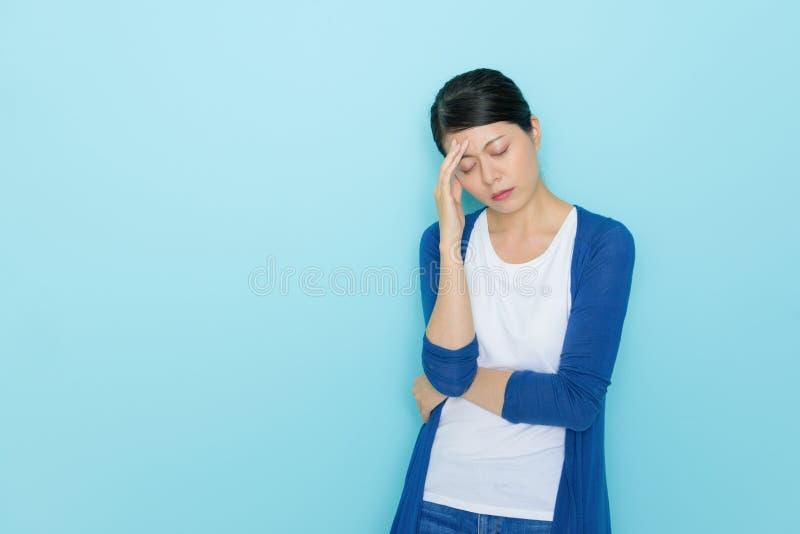 站立在蓝色背景中的女性办公室工作者 库存照片
