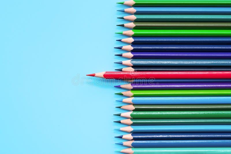 站立在蓝色背景的红色铅笔 领导,独特,独立,主动性,战略,异议,认为不同, 免版税库存图片