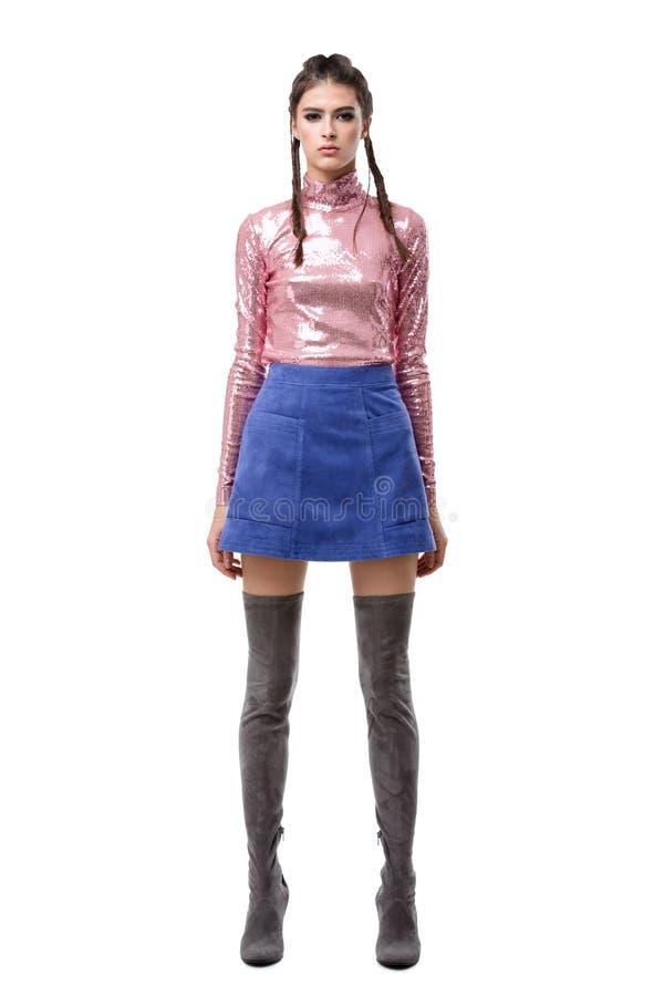 站立在蓝色裙子和桃红色上面的夫人与衣服饰物之小金属片和膝盖高的靴子在白色背景 库存照片