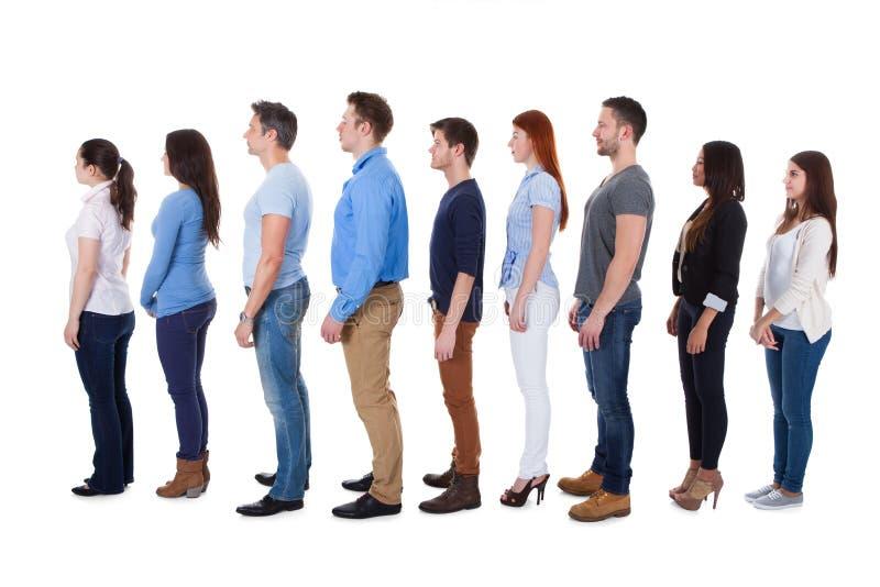 站立在行的不同的人 免版税库存图片