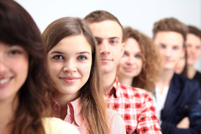 站立在行的愉快的微笑的学生 免版税库存图片