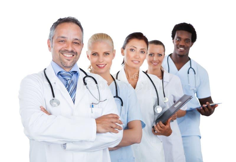 站立在行的确信的不同种族的医疗队 免版税库存图片