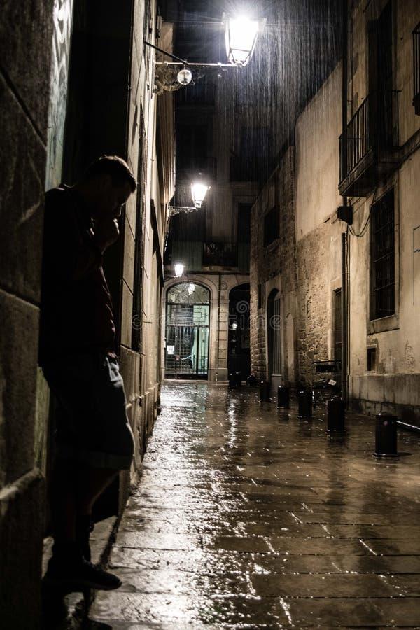 站立在街道上的一个人的剪影在哥特式处所在巴塞罗那在多雨夜、消沉和寂寞里 免版税库存照片