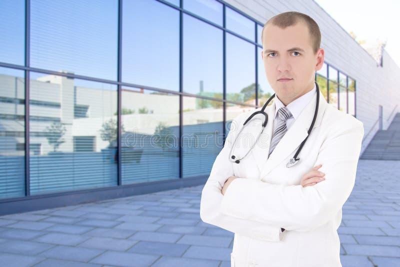 站立在街道上的男性医生反对现代医院大厦 库存照片