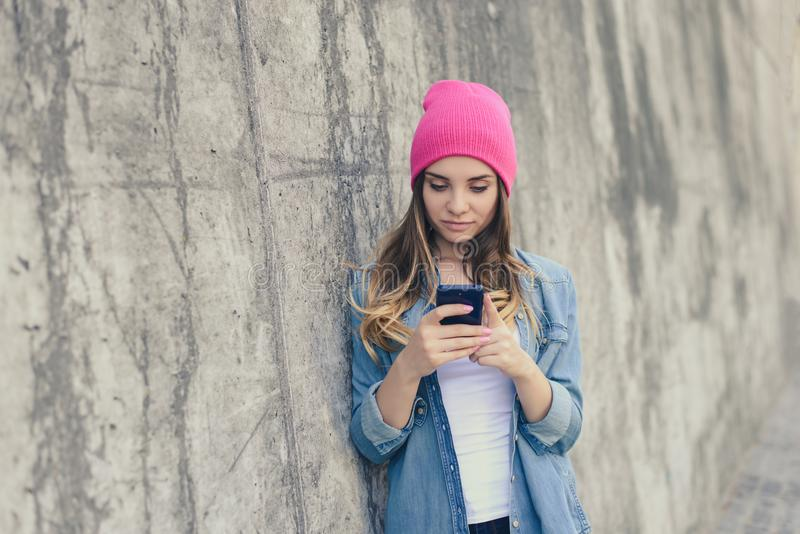 站立在街道上的近的墙壁和使用她的智能手机的便衣的逗人喜爱的美丽的女孩为通信在int中 免版税库存图片