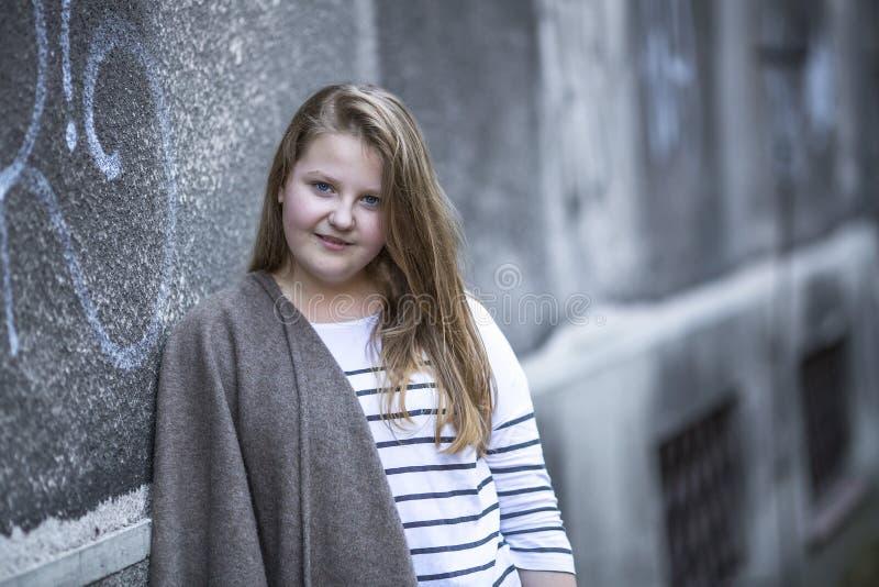 站立在街道上的逗人喜爱的青少年的女孩 库存照片