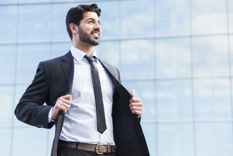 站立在衣服的阿拉伯商人或工作者在办公楼附近 库存图片