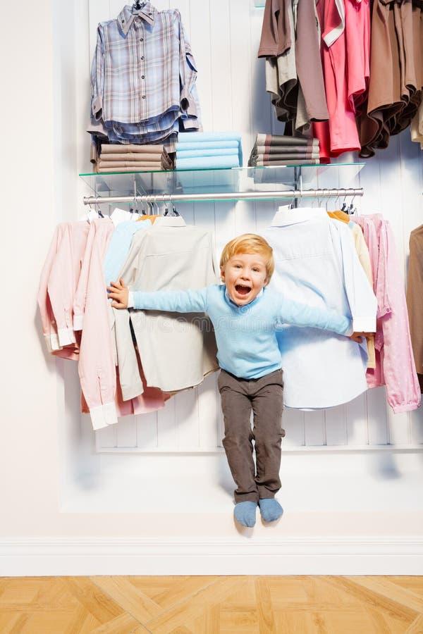 站立在衣裳中的笑的男孩在商店 库存照片