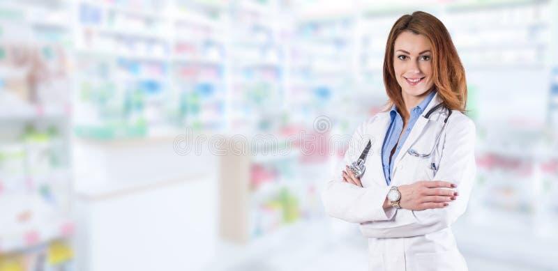 站立在被弄脏的药房内部的妇女医生 图库摄影