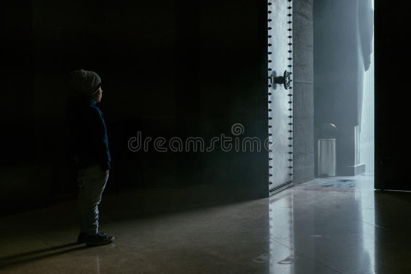 站立在被打开的门附近的小男孩 免版税库存照片
