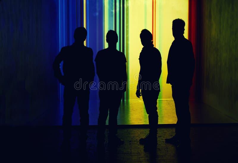站立在被突出的墙壁背景的四个人剪影  免版税图库摄影