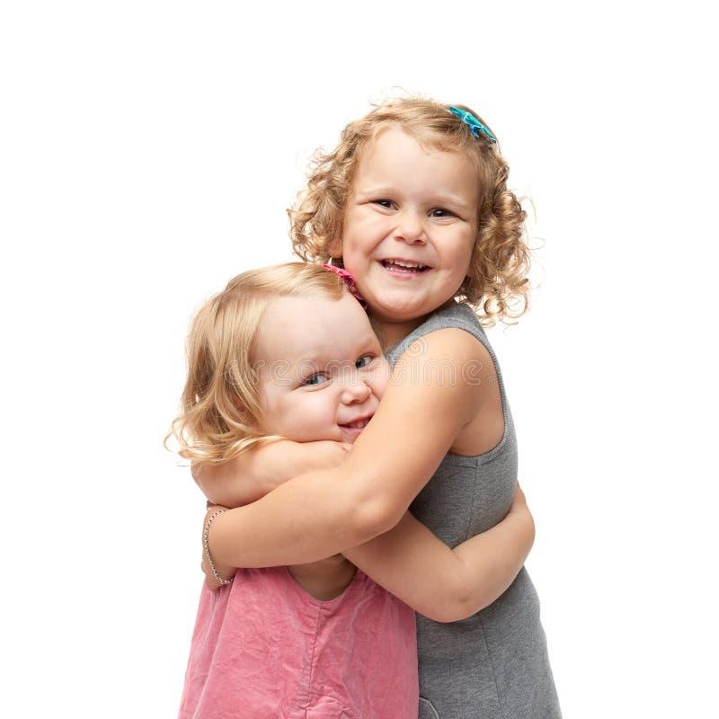 站立在被隔绝的白色背景的年轻小女孩夫妇  免版税库存照片