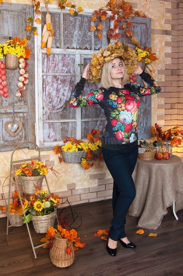 站立在装饰的家的秋天妇女 在ba的秋天静物画 库存图片