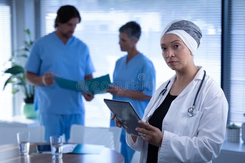 站立在诊所的成熟的女性医生,当拿着数字片剂时 库存照片