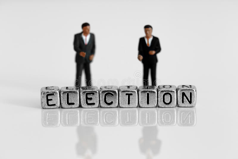站立在词候选人后的微型比例模型政客 库存图片