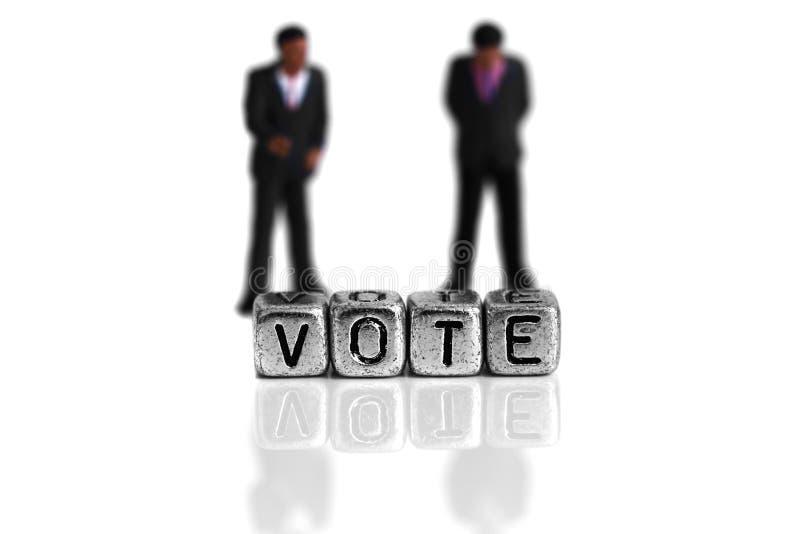 站立在词后的微型比例模型政客投票 库存照片