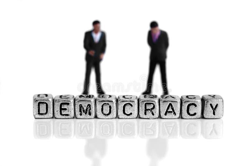 站立在词民主后的微型比例模型政客 免版税库存照片