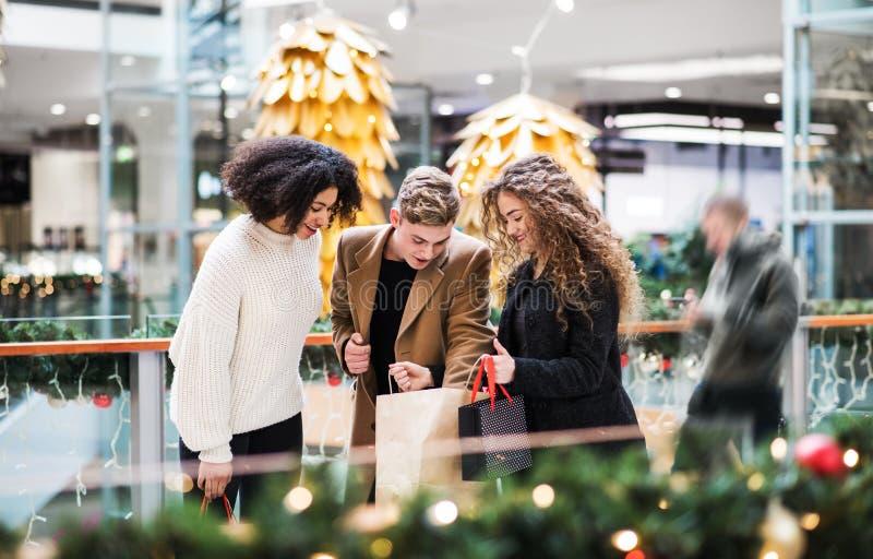 站立在购物中心的年轻朋友在圣诞节时间,看起来里面袋子 库存图片