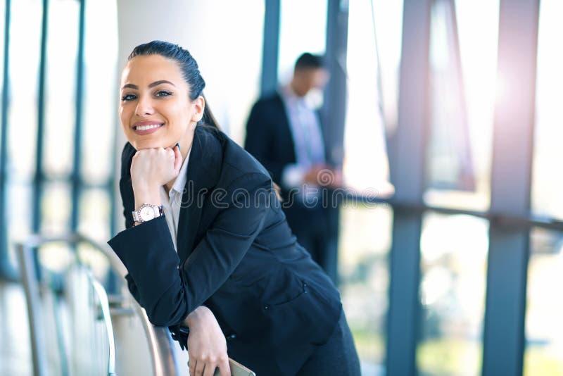站立在走廊的可爱的女商人 免版税库存图片