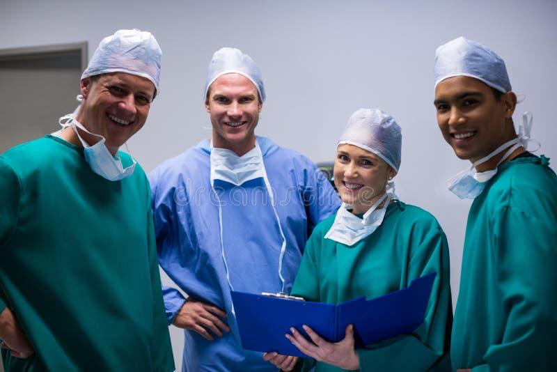 站立在走廊的外科医生队画象 图库摄影