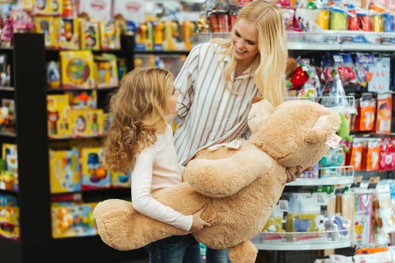 站立在超级市场的微笑的母亲和女儿 图库摄影