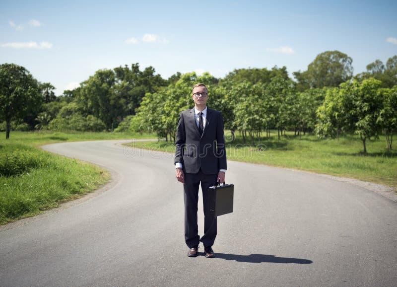 站立在路的商人 免版税库存图片