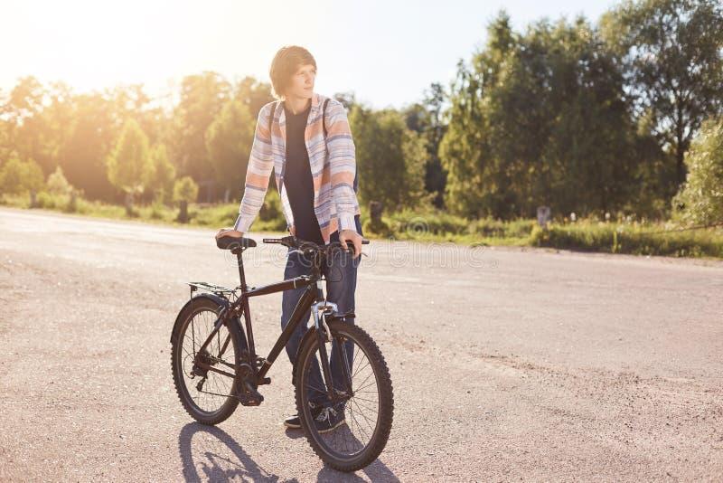 站立在路的沉思十几岁的男孩,保留在他的自行车把柄酒吧的手,一起等待其他骑自行车者有旅途 库存照片
