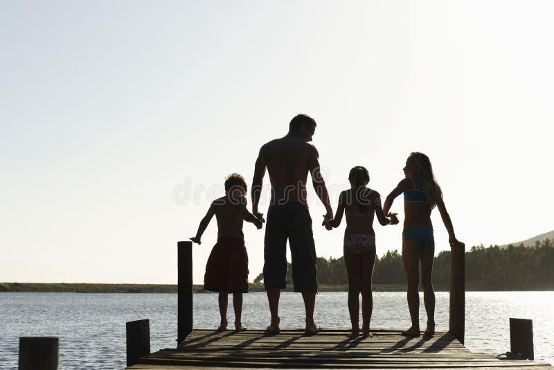 站立在跳船边缘的家庭  免版税库存照片