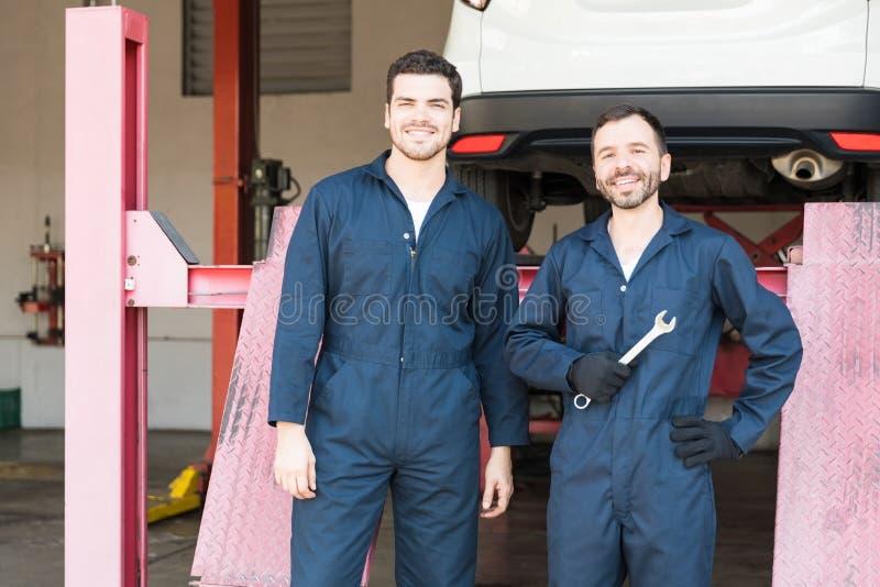 站立在车库的工作服的汽车修理师 免版税库存图片