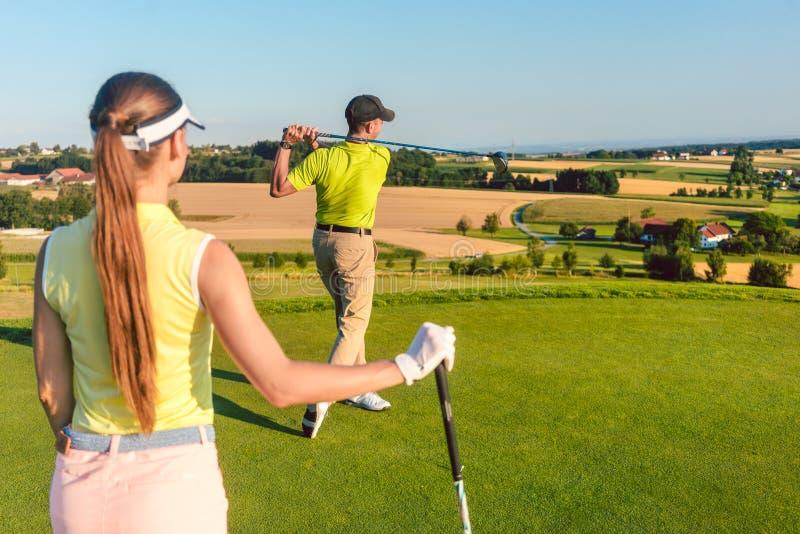 站立在远射射击的结束位置的职业高尔夫球运动员 库存照片