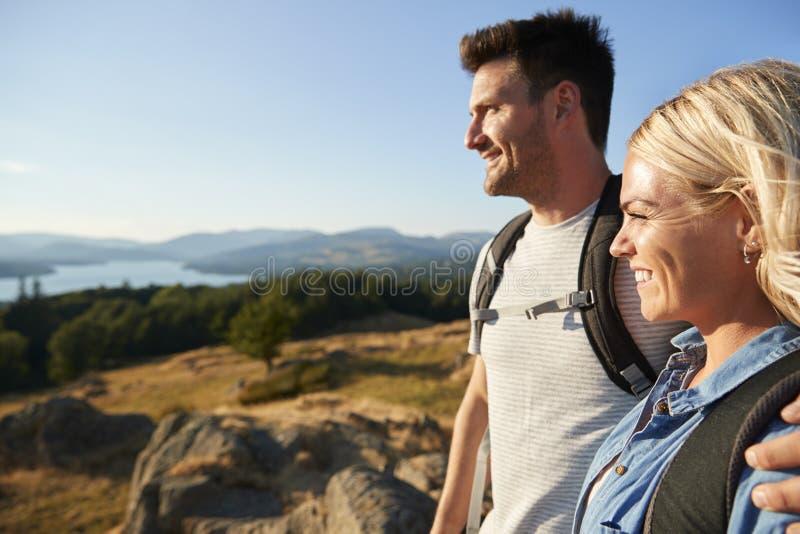站立在远足的小山顶部的夫妇通过乡下在湖区英国 库存图片