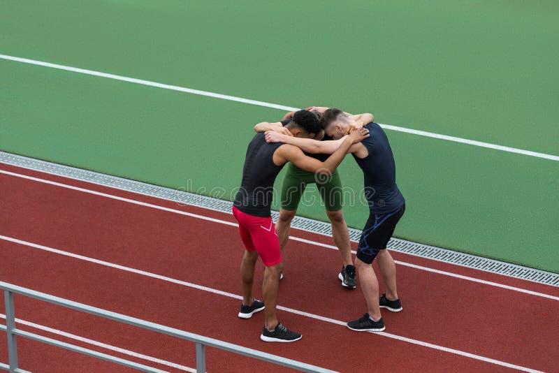 站立在连续轨道的英俊的不同种族的运动员队 免版税库存照片