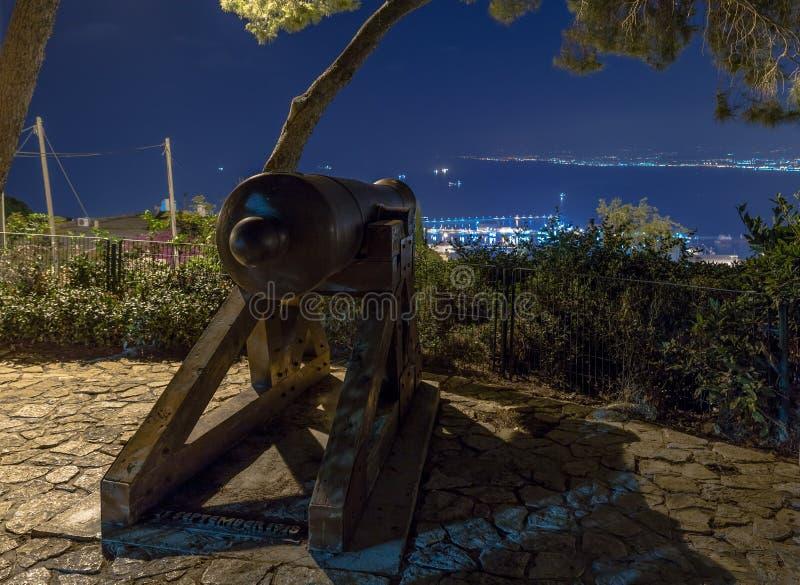 站立在迦密山的公园的纪念枪在海法和瞄准海法街市、港和海法海湾  免版税库存照片