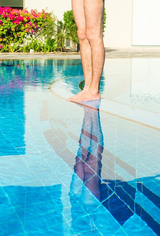 站立在透明的游泳池的脚 库存照片