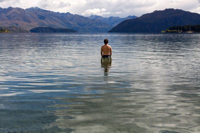 站立在遥远的湖的人 免版税库存图片
