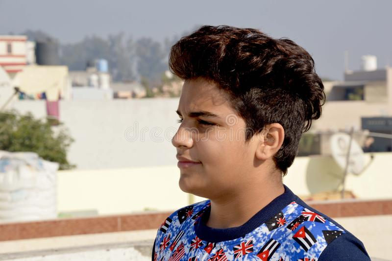 站立在采取的sunbath房子屋顶的十几岁的男孩 免版税库存图片