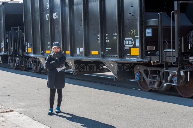 站立在采煤车旁边的亚裔妇女 库存图片