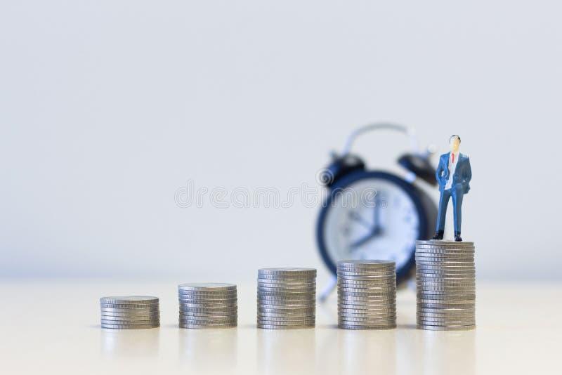 站立在金钱硬币堆的微型人商人 金钱和财政概念 能承受的财务 库存照片