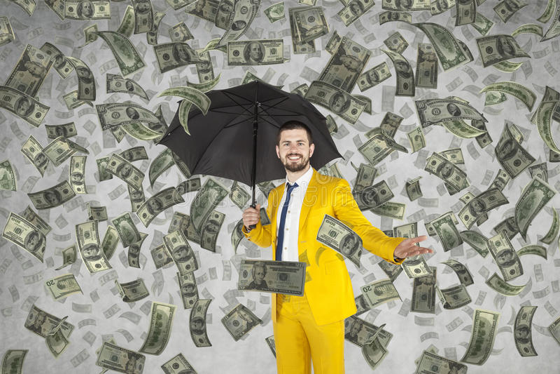 站立在金钱雨中的年轻富有的商人 免版税库存照片