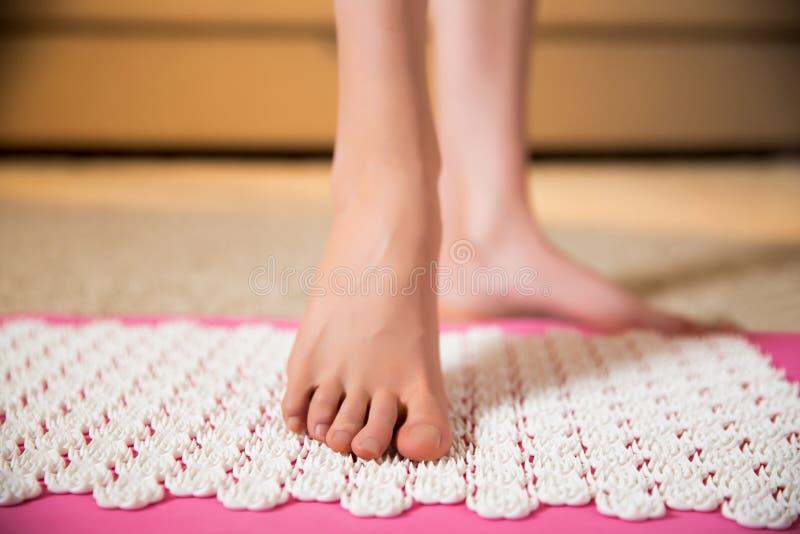 站立在针压法席子的女性脚 库存图片