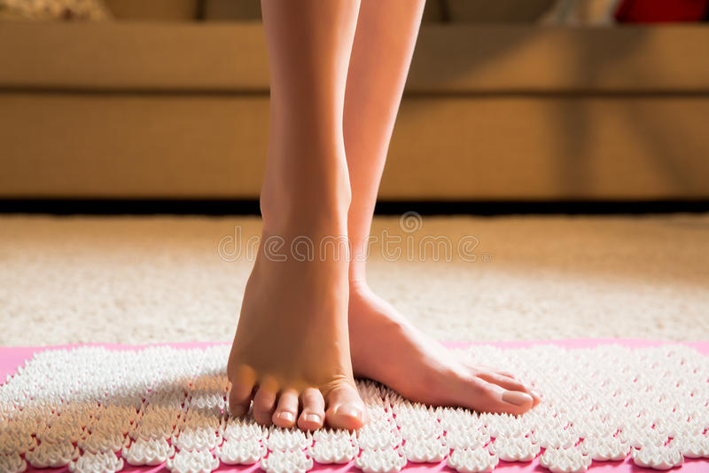 站立在针压法席子的女性脚 库存照片